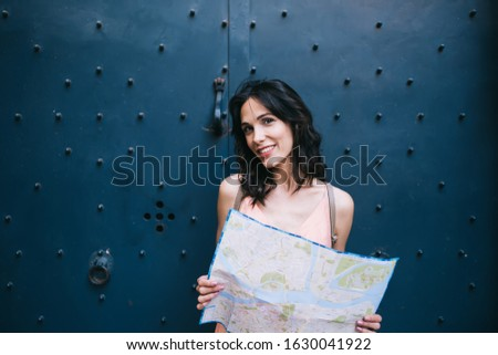 Cheerful young woman with map of city smiling and looking at camera while standing against blue gate on ancient street