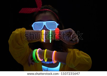 Cheerful young woman with neon bracelets in dark room #1107231647