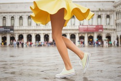 Cheerful young woman with sexy legs and yellow skirt