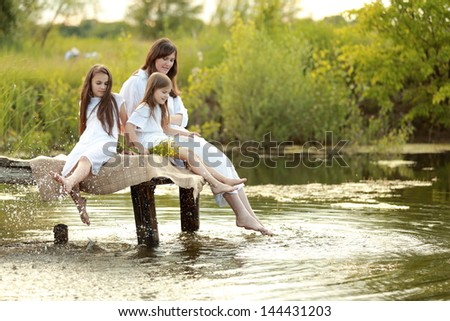 Cheerful young woman with two young girls sitting on a pier at the lake on the background of beautiful nature in spring