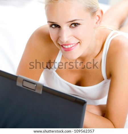 Cheerful young woman working with laptop, at home