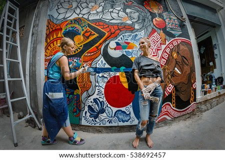 Cheerful young women painting on the wall.