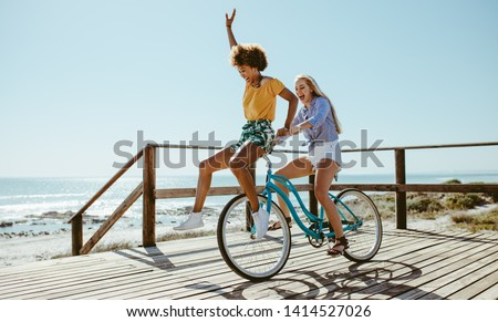 Cheerful young women taking a bike ride together at the beach. Female friends having fun on a bike at the seaside boardwalk.