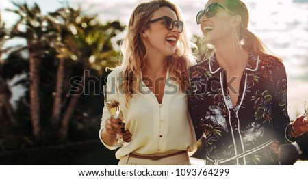 Cheerful young women walking together with glass of wine. Stylish female friends enjoying themselves outdoors.