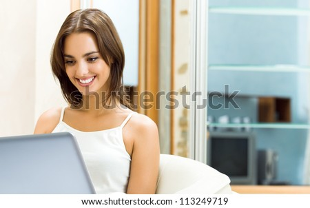 Cheerfull smiling woman working with laptop, at home, with copyspace