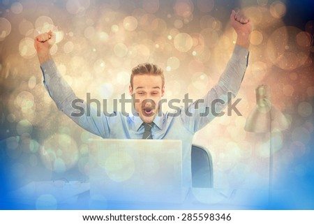 Cheering businessman at laptop against light glowing dots design pattern