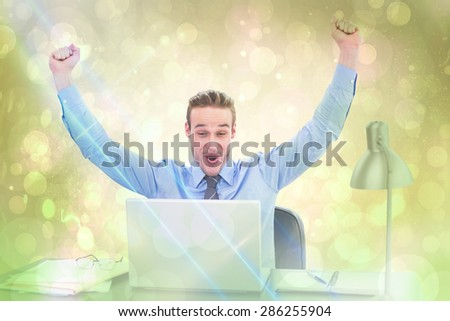Cheering businessman at laptop against yellow abstract light spot design
