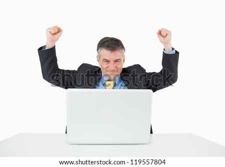 Cheering businessman sitting at his desk with his laptop on white background