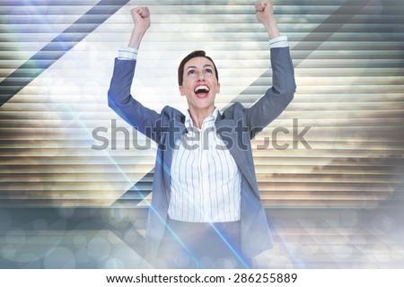 Cheering businesswoman against window overlooking city