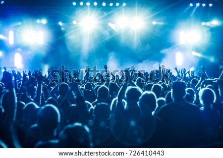 cheering crowd at rock concert in front of bright lights #726410443