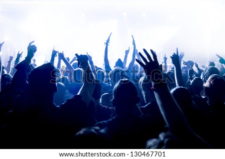 cheering crowd in front of bright blue stage lights