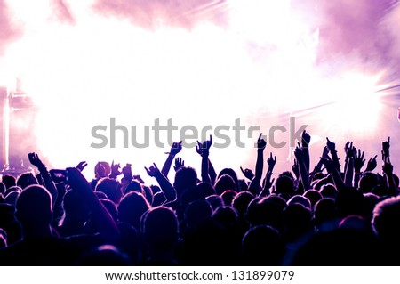 cheering crowd in front of bright purple stage lights #131899079