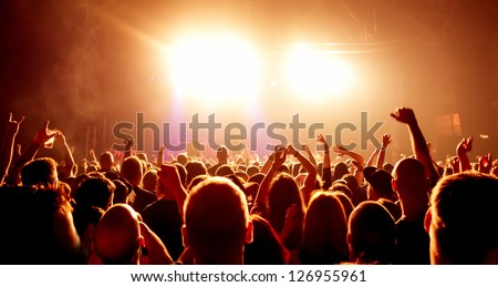 cheering crowd in front of bright yellow stage lights #126955961