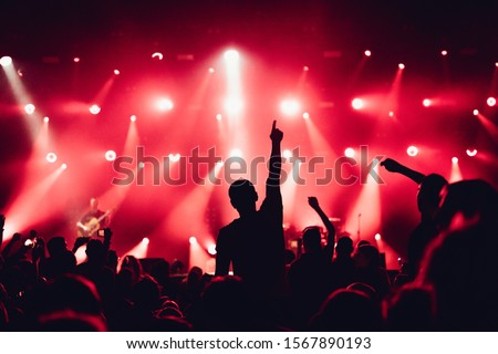cheering crowd of unrecognized people at a rock music concert. crowd in front of bright stage lights. Concert audience at music concert. Smoke, concert spotlights.