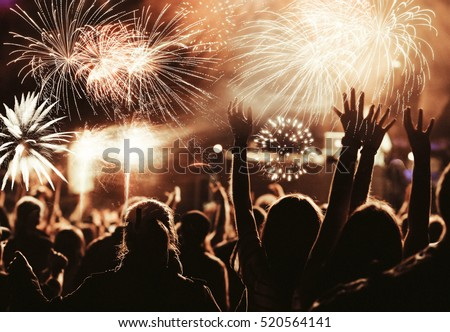 cheering crowd watching fireworks at New Year - holiday celebration background #520564141