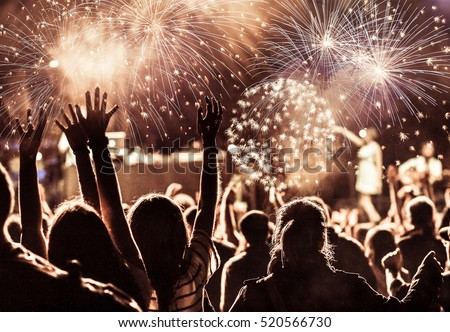 cheering crowd watching fireworks at New Year - holiday celebration background #520566730