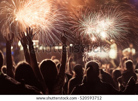 cheering crowd watching fireworks at New Year - holiday celebration background #520593712