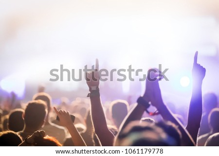 Cheering crowd with hands in air at music festival #1061179778