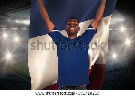 Cheering football fan in blue jersey holding france flag against large football stadium with fans in blue