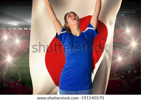 Cheering football fan in blue jersey holding japan flag against vast football stadium with fans in red