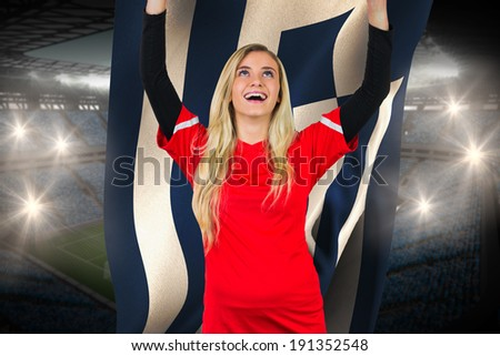 Cheering football fan in red holding greece flag against large football stadium with fans in blue