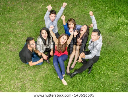 cheering group of friends holding hands up outdoors