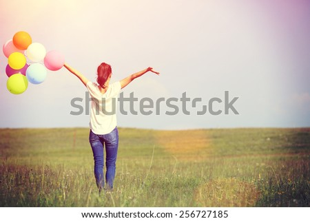cheering happy woman on green grassland with colored balloons