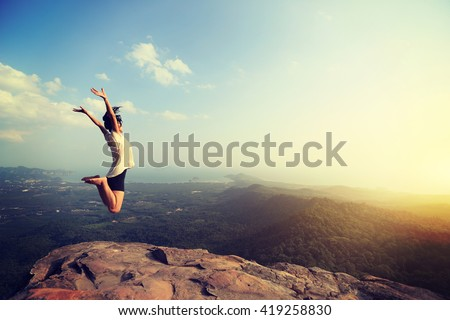 cheering happy young asian woman jumping on mountain peak cliff edge #419258830