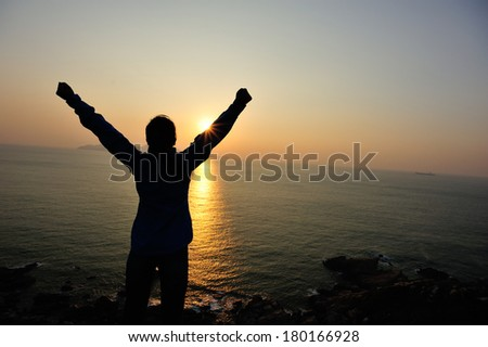 cheering hiking woman open arms to the sunrise stand at seaside mountain