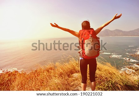 cheering hiking woman stand mountain peak looking at the view with arms open