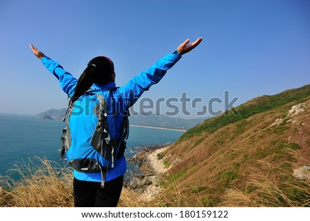 cheering hiking woman stand seaside rock looking the view with arms open