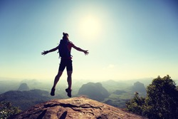 cheering successful young woman hiker jumping on mountain top cliff edge
