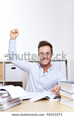 Cheering university student with clenched fist at desk with many books