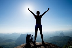 Cheering woman backpacker enjoy the view on sunrise mountain top cliff edge