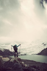 Cheering woman backpacker hiking in winter high altitude mountains