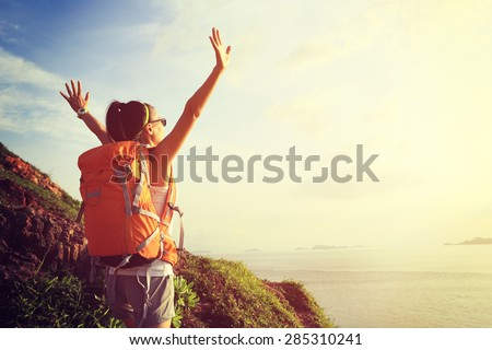 cheering woman backpacker on  seaside mountain  enjoy the view