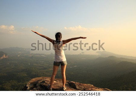 cheering woman open arms at mountain peak