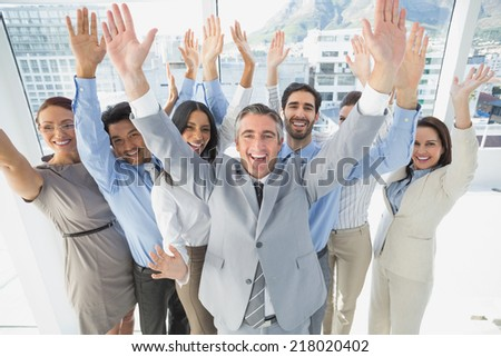 Cheering workers with raised arms in the office