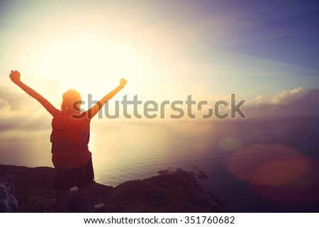 cheering young woman backpacker at sunrise seaside mountain peak