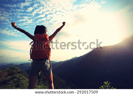 cheering young woman backpacker enjoy the view at mountain peak