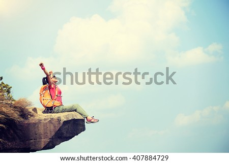 cheering young woman hiker enjoy the view at mountain peak cliff #407884729