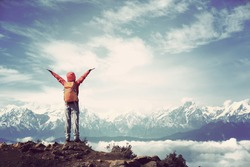 cheering young woman hiker open arms to beautiful snow mountain summits