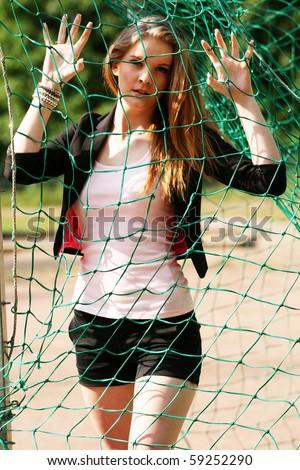 Cheerleader at net practice, sunlit composition