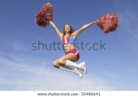 Cheerleader in jumping with pom poms raised, mid air