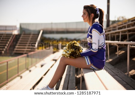 Cheerleader sitting in sports stadium looking across the field.