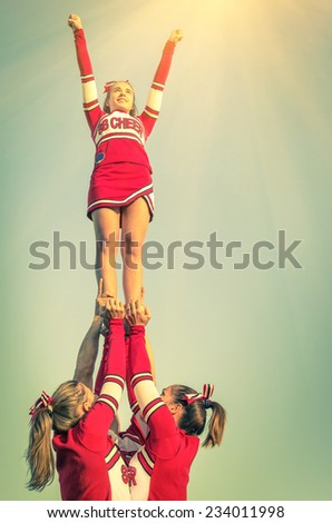 Cheerleaders in action on a vintage filtered look - Concept of unity and team sport - Training at college high school with young female teenagers