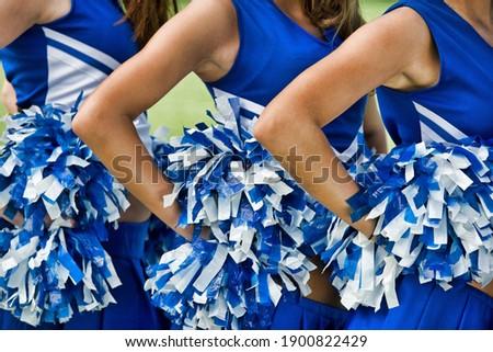Cheerleaders in Uniform Holding Pom-Poms ストックフォト ©