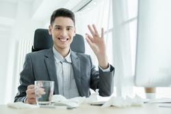 Cheerless man taking pills in the office