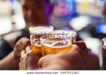 Cheers! Clink glasses. Close-up pictures of hands holding a beer glass in a happy birthday celebration.