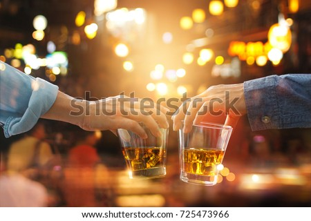 Cheers clinking of friends with bourbon whisky drink in party night after work on colorful background